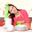 Beautiful young womwipes cleutensils in kitchen — Stock Photo #38220237