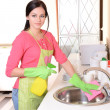 Beautiful young womcleans in kitchen — Stock Photo #38220267