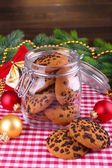 Delicious Christmas cookies in jar on table on wooden background — Zdjęcie stockowe