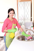 Beautiful young woman cleans in kitchen — Foto Stock
