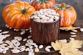 Pumpkin seeds in pot with pumpkins on wooden background — Stock Photo