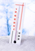 Thermometer in snow on light background — Stock Photo