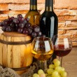 Stock Photo: Composition of wine and grapes on wooden barrel on table on brick wall background