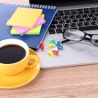 Stock Photo: Laptop with stationery and cup of coffee on table