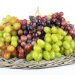 Fresh grape on wicker mat isolated on white — Stock Photo
