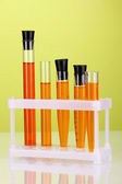 Test-tubes with a colorful solution on green background close-up — Stock Photo