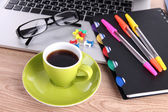 Laptop with stationery and cup of coffee on table — Stock Photo