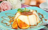 Panna Cotta with orange zest and caramel sauce, on color wooden background — Stock Photo