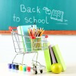 Stock Photo: School supplies in supermarket cart on blackboard background