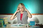 Tired chemistry teacher sitting at table on blackboard background — Stock Photo