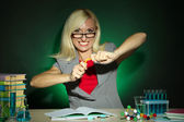 Wicked chemistry teacher sitting at table on dark colorful background — Stock fotografie
