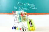 School supplies in supermarket cart on blackboard background — Foto de Stock