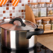 Pot on stove in kitchen on table on mosaic tiles background — Stok fotoğraf