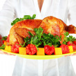 Chef holding a plate of baked chicken with vegetables close-up — Stock Photo