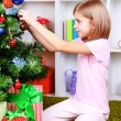 Little girl sitting near Christmas tree in room — Stock Photo #38369779