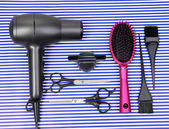 Hairdressing tools on striped blue background — Stock Photo