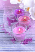 Beautiful colorful candles and orchid flowers, on color wooden background — Stock Photo