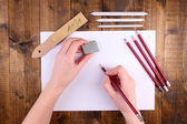 Hands holding pencil and erase with art materials on wooden background — Stock Photo