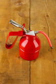 Red oil can, on wooden background — Stock Photo