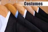 Suits with shirts on hangers on wooden background — Foto de Stock