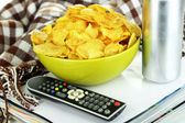 Chips in bowl, magazines, plaid and TV remote close-up — Stock Photo