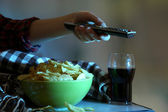 Someone watching TV with crisps and cola in room — Stock Photo