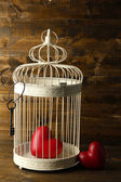 Hearts in decorative cage on wooden background — Stock Photo