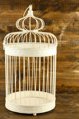 Beautiful decorative cage, on wooden background — Stock Photo