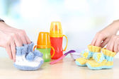 Hands with crocheted booties for baby, on light background — ストック写真