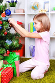 Little girl sitting near Christmas tree in room — Stock Photo