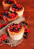 Tasty muffins with berries on wooden table — Stock Photo