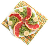 Assortment of sliced fruits on plate, isolated on white — Fotografia Stock