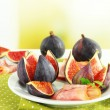 Tasty figs with ham on white wooden table — Stock Photo