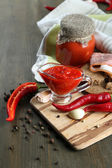 Composition with salsa sauce on bread,, red hot chili peppers and garlic, on napkin, on wooden background — Stock Photo