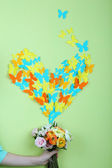 Paper butterflies fly out of flowers on green wall background — Stock Photo