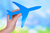 Toy airplane in hand on light blue background — Stock Photo