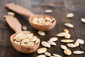 Pumpkin seeds in spoons on wooden background — Stock Photo