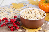 Pumpkin seeds in bowl with pumpkin on table close up — 图库照片