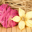Decorative straw for hand made, flower and heart of straw, on wooden background — Stock Photo #38477949