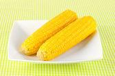 在绿色的桌布上的白板上的煮的玉米 — 图库照片