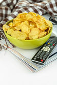 Chips in bowl and TV remote isolated on white — Zdjęcie stockowe