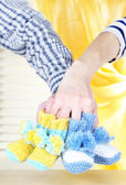 Hands with crocheted booties for baby, on light background — Stock Photo