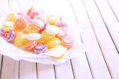 Sweet multicolor candies on paper, on color wooden background — Stock Photo