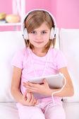 Liten flicka lyssnar musik sitter på soffan i rummet — Stockfoto
