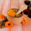 Medicine bottles and calendula flowers on wooden background — Stock Photo #38595215