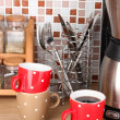 Постер, плакат: Cups and coffee maker in kitchen on table on mosaic tiles background