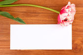 Beautiful tulip and card on wooden background — Stock Photo