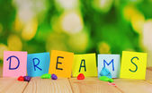 "The word ""Dreams"" on wooden table on natural background — Stock Photo"