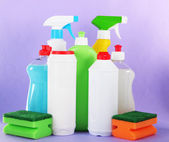 Different kinds of kitchen cleaners and colorful sponges, on color background — Stock Photo