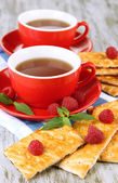 Cups of tea with cookies and raspberries on table close-up — Stock Photo